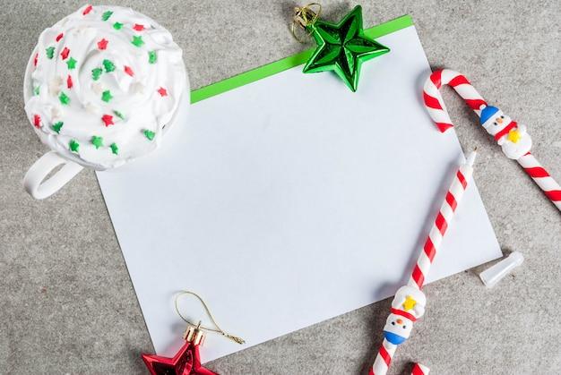 Uma mesa cinza com uma folha de saudação, decorações de natal, uma xícara de chocolate quente e caneta em forma de pirulito. menina escrevendo, mão feminina na foto, vista superior, efeito de neve