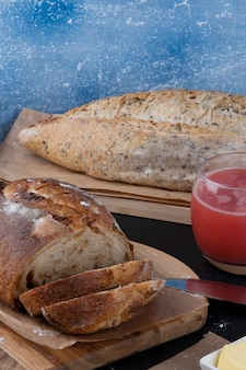 Uma mesa com deliciosos pães assados e suco de melancia.