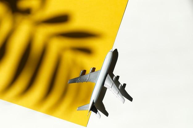 Uma mesa com papel amarelo e um avião de brinquedo, uma sombra de uma palmeira