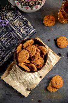 Uma mesa com vista superior com chaleira e biscoitos dentro do prato