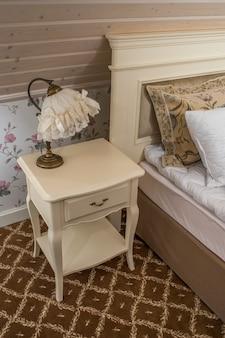 Uma mesa de cabeceira com uma lâmpada no quarto