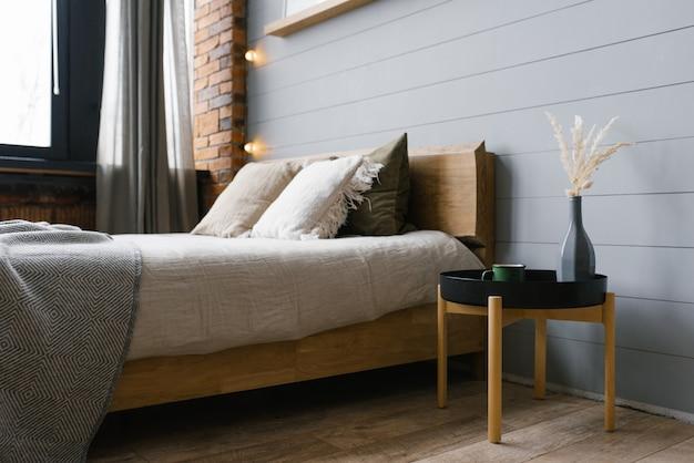 Uma mesa de cabeceira preta com um vaso cinza e flores secas e uma caneca de metal verde colocada ao lado da cama em uma foto real do interior de um quarto cinza em estilo escandinavo