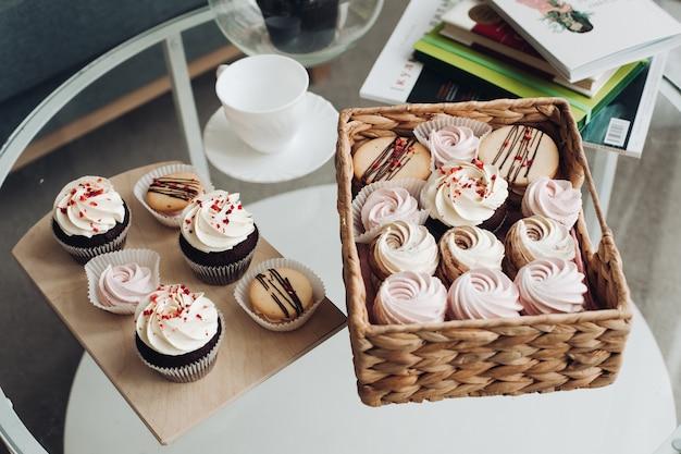 Uma mesa de café da manhã com uma xícara de café, doces, marshmallows e biscoitos