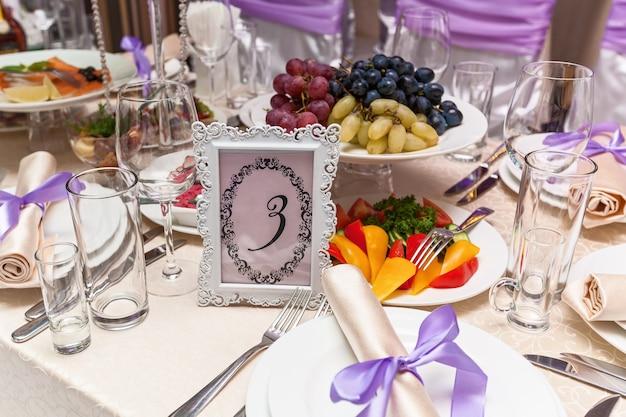 Uma mesa de casamento decorada com assento número cinco. mesa de casamento servida.