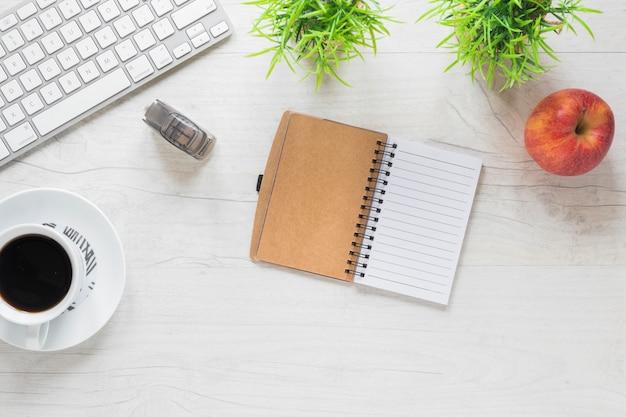 Uma mesa de escritório com diário; xícara de café; maçã; grampeador e teclado na mesa de madeira