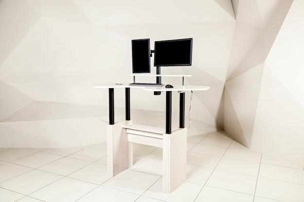 Uma mesa de escritório com dois manitores um mecanismo de levantamento para o titular do manitor