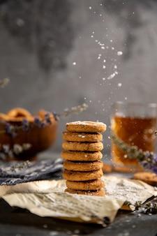 Uma mesa de frente com biscoitos e com chá na mesa cinza biscoito chá biscoito doce