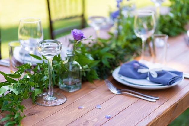 Uma mesa de madeira sem toalha de mesa é servida e decorada com flores frescas. café ao ar livre