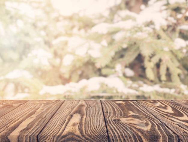 Uma mesa de madeira vazia com árvores desfocadas