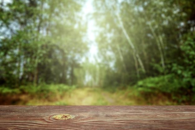Uma mesa de madeira vazia com vista para um bokeh verde turva, cópia espaço