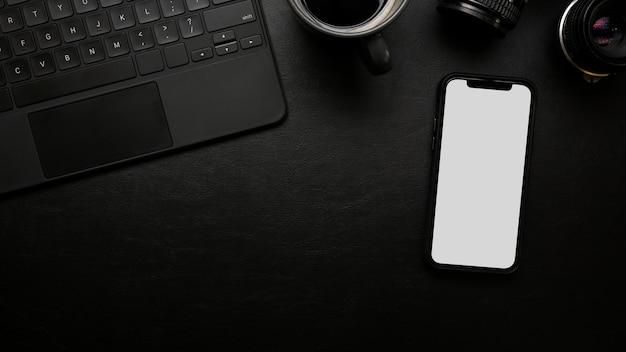 Uma mesa de trabalho com um moderno teclado de maquete de tela em branco para celular em uma superfície de couro preto