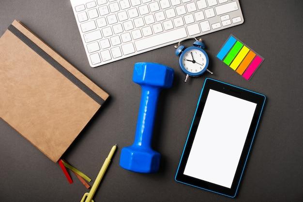 Uma mesa escura com um planejador, um peso azul, um tablet, um teclado para tornar o tempo mais produtivo