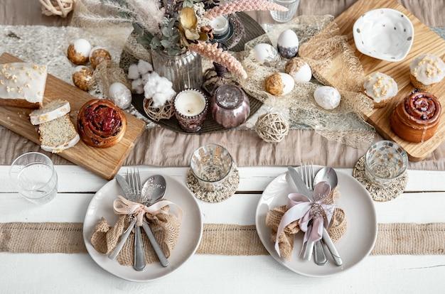 Uma mesa festiva com belos pratos, artigos de decoração e pastelaria. idéia de design de configuração de mesa de páscoa.