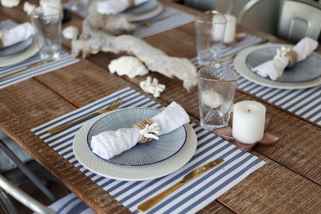 Uma mesa prateada. pratos e aparelhos em estilo de madeira. mesa, cadeiras.