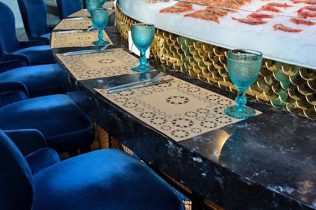 Uma mesa redonda servida, localizada ao redor da cozinha aberta em um restaurante de peixe.