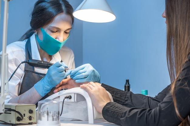 Uma mestra de manicure no salão trabalhando com as unhas da cliente em um fundo azul