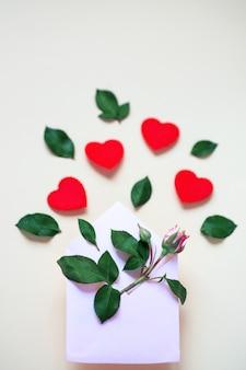 Uma miniatura de flor rosa com folhas e corações encontra-se em um envelope. sobre um fundo claro. conceito dia dos namorados.