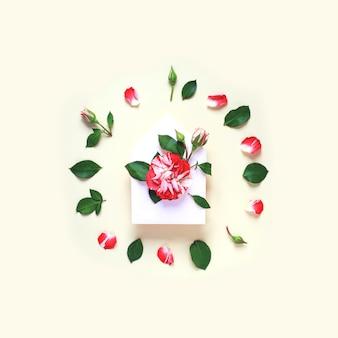 Uma miniatura de flor rosa com folhas e pétalas está no envelope.