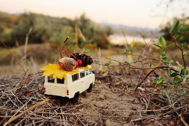 Uma minivan de carro de brinquedo pequeno carrega no telhado uma bolota