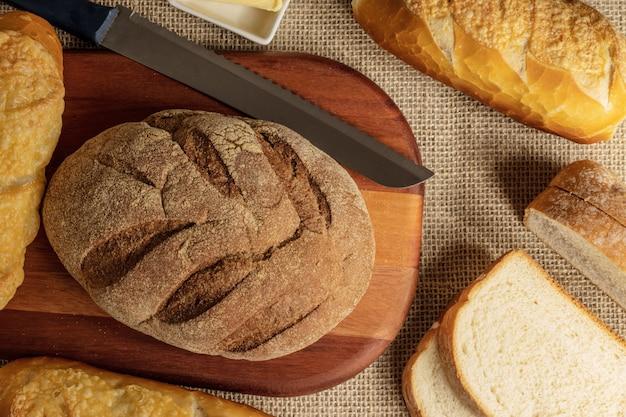 Uma mistura de diferentes tipos de pães na mesa.