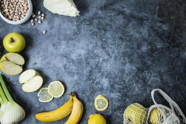 Uma mistura de frutas da estação amarelas, legumes e grãos integrais, colocados sobre um fundo escuro com copyspace
