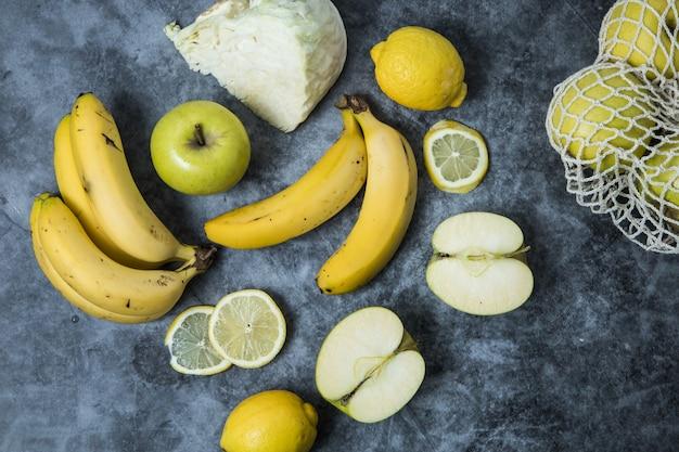 Uma mistura de frutas e legumes amarelos dispostos sobre uma superfície escura