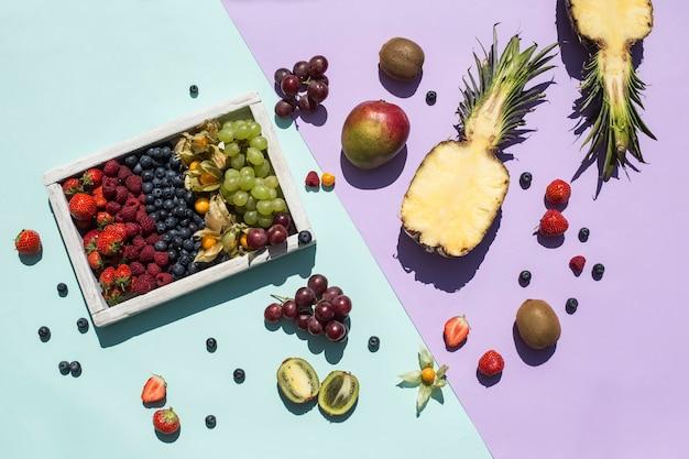 Uma mistura de frutas frescas e bagas em uma caixa de madeira e em um fundo verde e roxo brilhante. os trópicos. alimentos saudáveis para uma dieta. vitaminas. vista superior com um espaço de cópia. orientação horizontal.