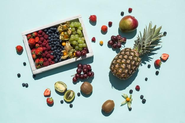 Uma mistura de frutas frescas e bagas em uma caixa de madeira e sobre um fundo de cor brilhante. os trópicos. alimentos saudáveis para uma dieta. vitaminas. vista superior com um espaço de cópia. orientação horizontal.