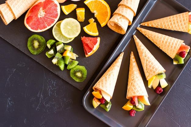 Uma mistura de frutas maduras cortadas em uma placa e cones de waffle para o feriado. vista do topo. fundo preto.
