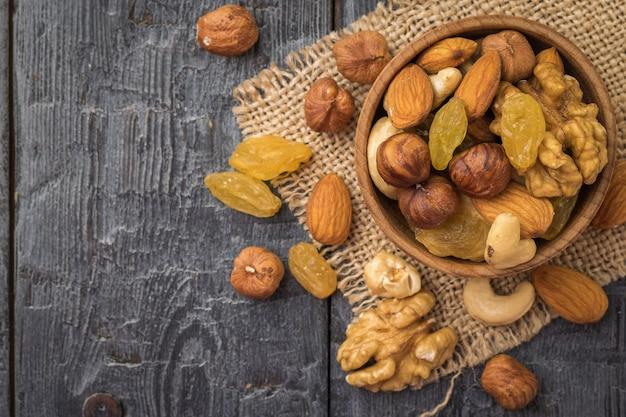 Uma mistura de frutas secas e nozes em uma tigela de madeira em um pedaço de serapilheira sobre uma mesa de madeira. comida vegetariana natural e saudável. postura plana.