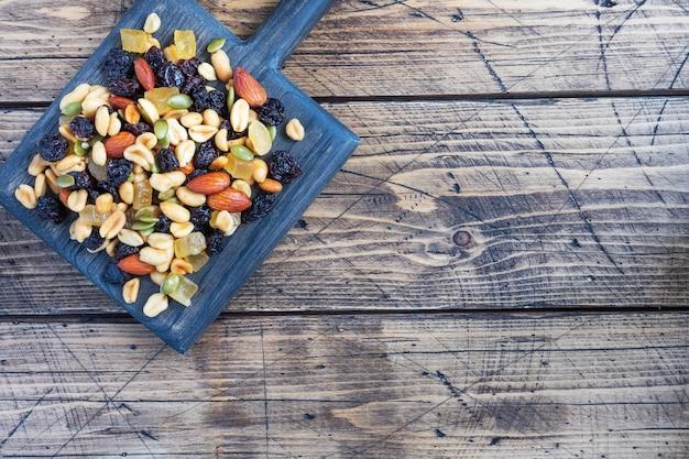 Uma mistura de nozes e frutas secas em uma tábua de madeira, fundo rústico. conceito de alimentação saudável. copie o espaço