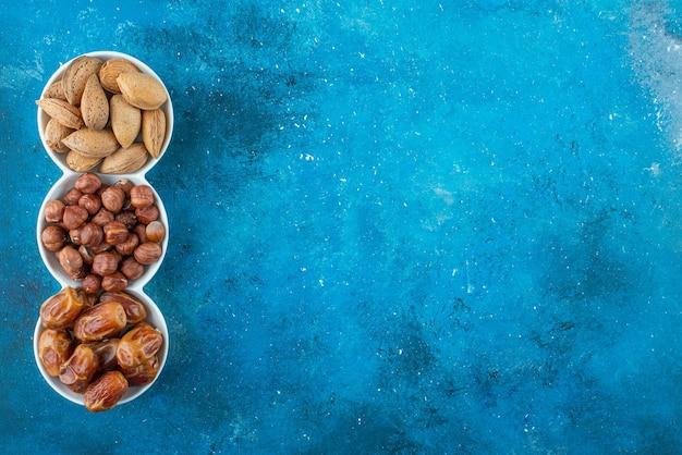 Uma mistura de nozes em uma tigela, na mesa azul.