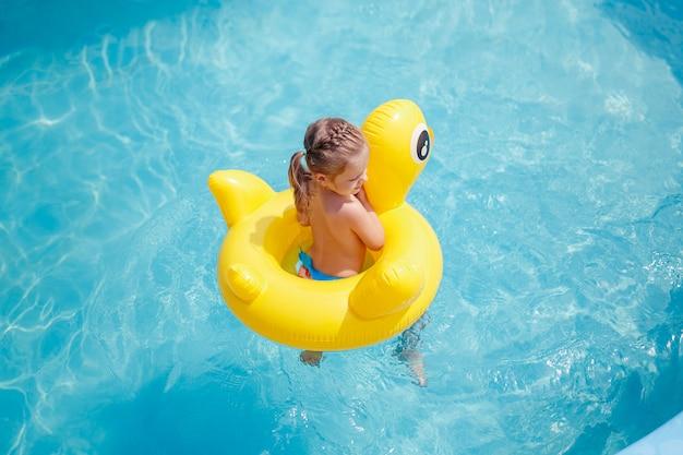 Uma moça nada em uma piscina em um colete salva-vidas amarelo