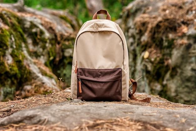 Uma mochila turística da moda na floresta o conceito de caminhada