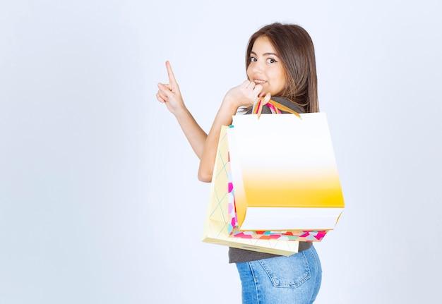 Uma modelo de jovem carregando suas sacolas de compras e apontando para cima.