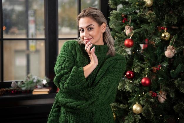 Uma modelo de mulher bonita com um suéter verde posando perto da árvore de natal