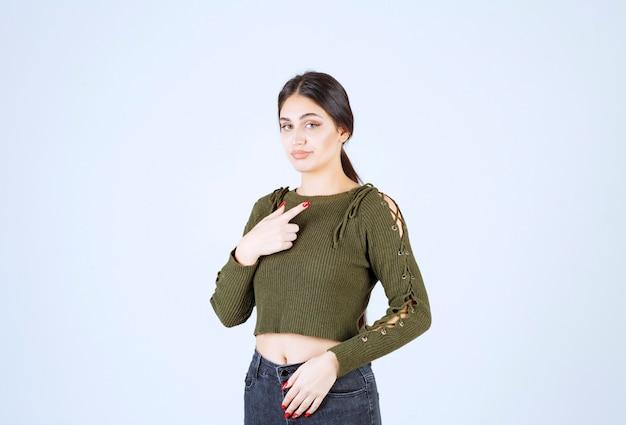Uma modelo de mulher chocada apontando os dedos para si mesma sobre um fundo branco.