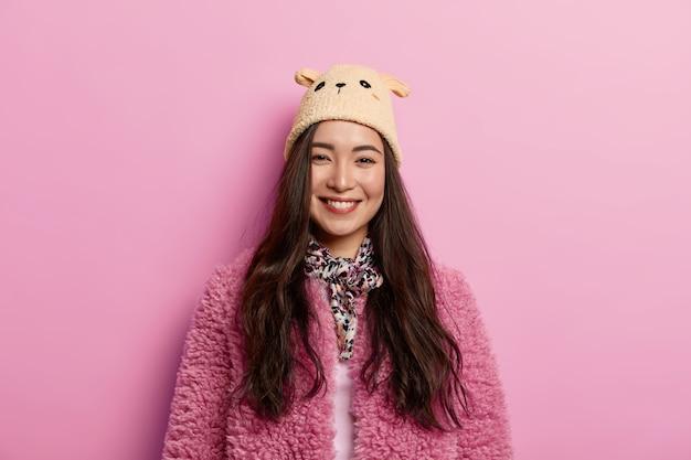 Uma modelo feminina asiática muito alegre olha diretamente para a câmera com um sorriso radiante e cheio de dentes e expressa boas emoções
