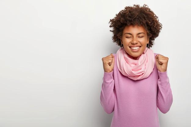 Uma modelo feminina satisfeita e feliz levanta os punhos enquanto celebra algo, usa uma blusa de gola alta roxa e mantém os olhos fechados