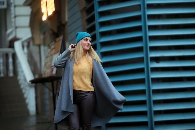 Uma modelo feminina sorri na rua vestindo um casaco e uma blusa amarela
