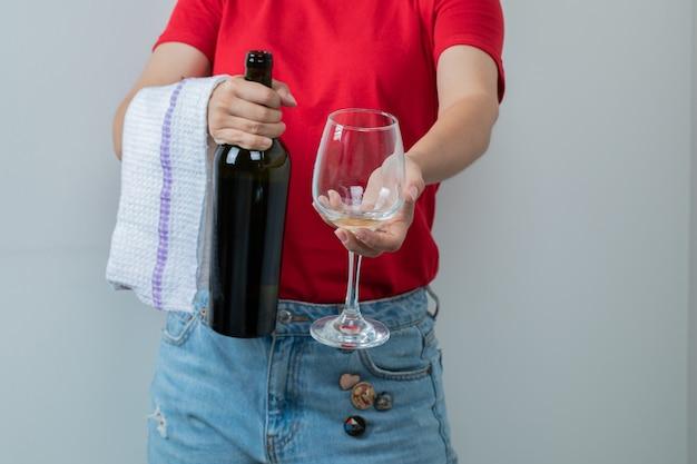 Uma modelo segurando uma garrafa de vinho e um copo