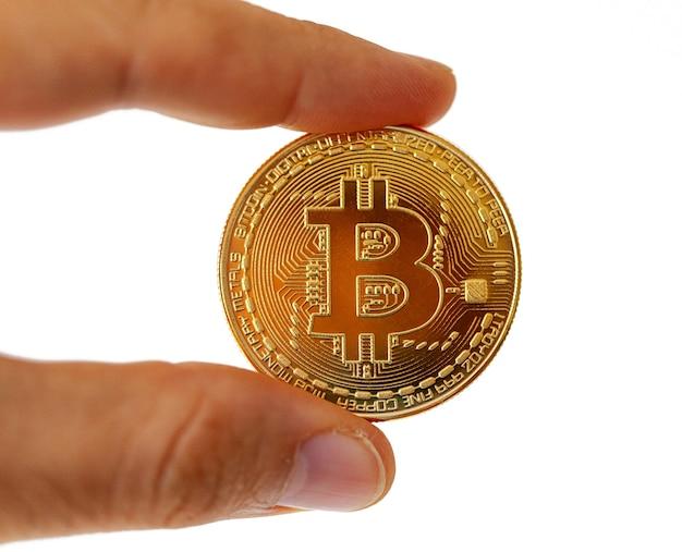 Uma moeda bitcoin entre seus dedos. assunto isolado na parede branca.