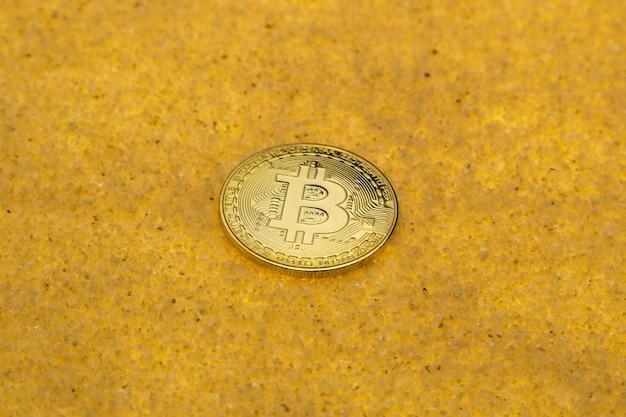Uma moeda criptográfica bitcoin em um fundo de areia dourada brilhante com luz de fundo