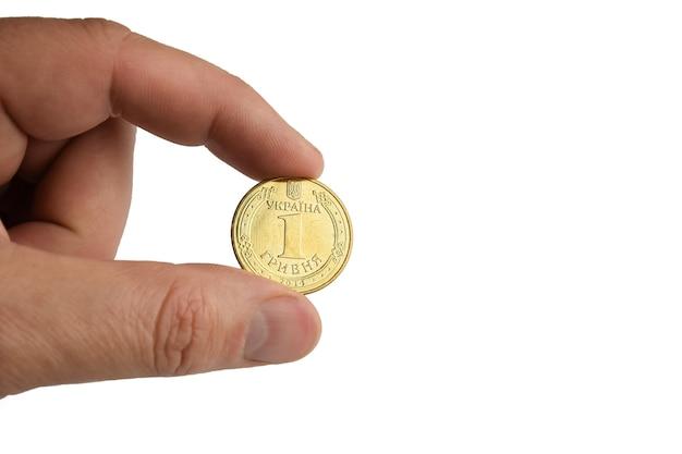 Uma moeda de ferro amarela presa por dois dedos em um fundo branco
