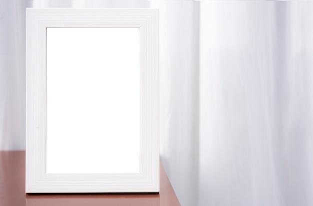 Uma moldura branca em branco empoleirada no canto da mesa. cortina branca de fundo na sala