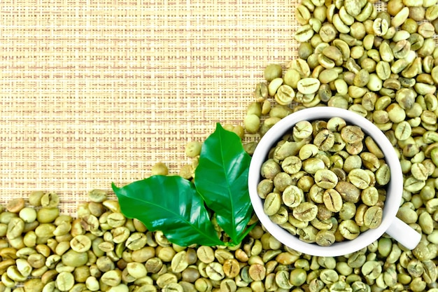 Uma moldura de grãos de café verdes com folhas e uma xícara em um tecido amarelo grosso