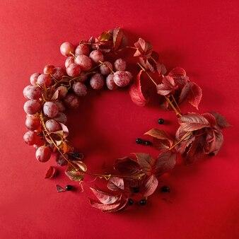 Uma moldura de uvas vermelhas e folhas de videira