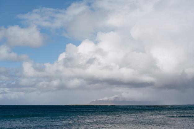 Uma montanha coberta de neve na costa atlântica na islândia, vista do outro lado ou do mar