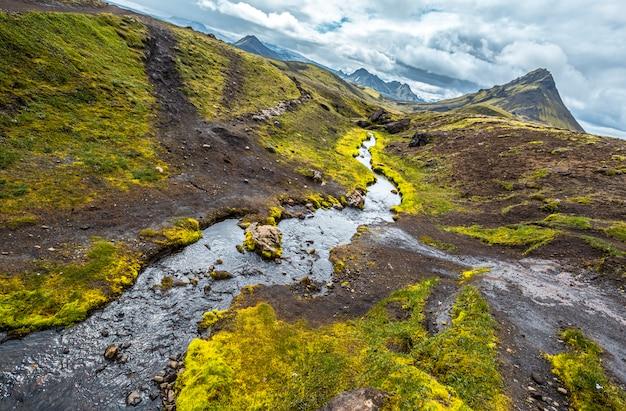 Uma montanha verde com um belo rio na caminhada de 54 km de landmannalaugar, islândia