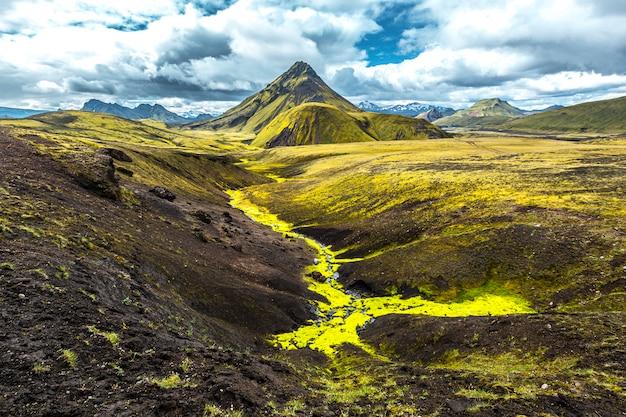 Uma montanha verde e um rio de musgo na caminhada de 54 km de landmannalaugar, islândia